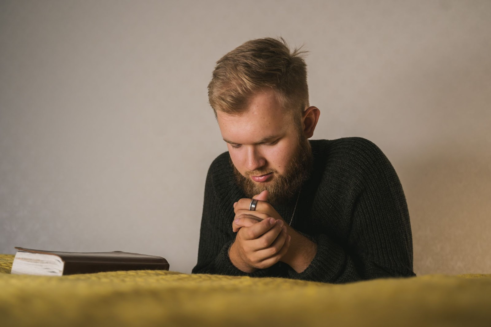 A young man prays at his bedside with a Bible