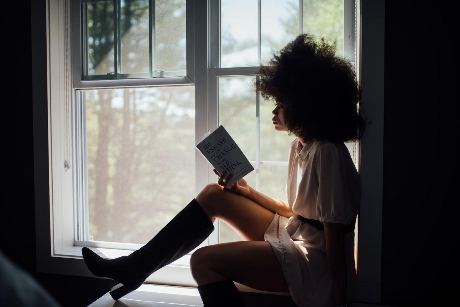 Woman reading alone on a windowsill
