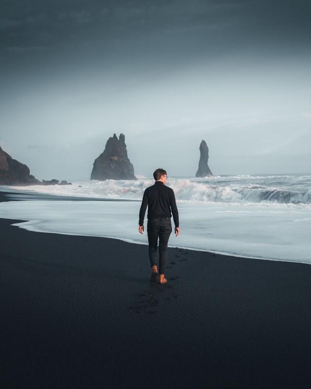 Man walking on beach barefoot