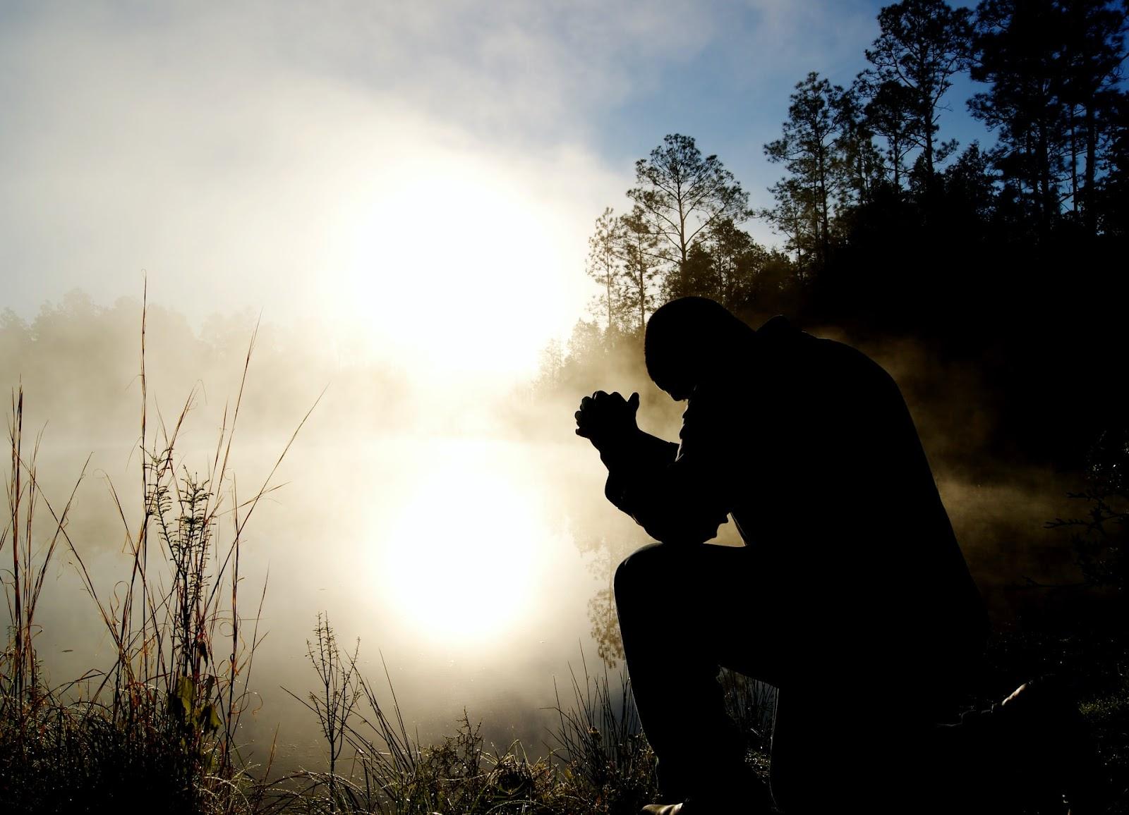 silhouette of a man praying by a lake