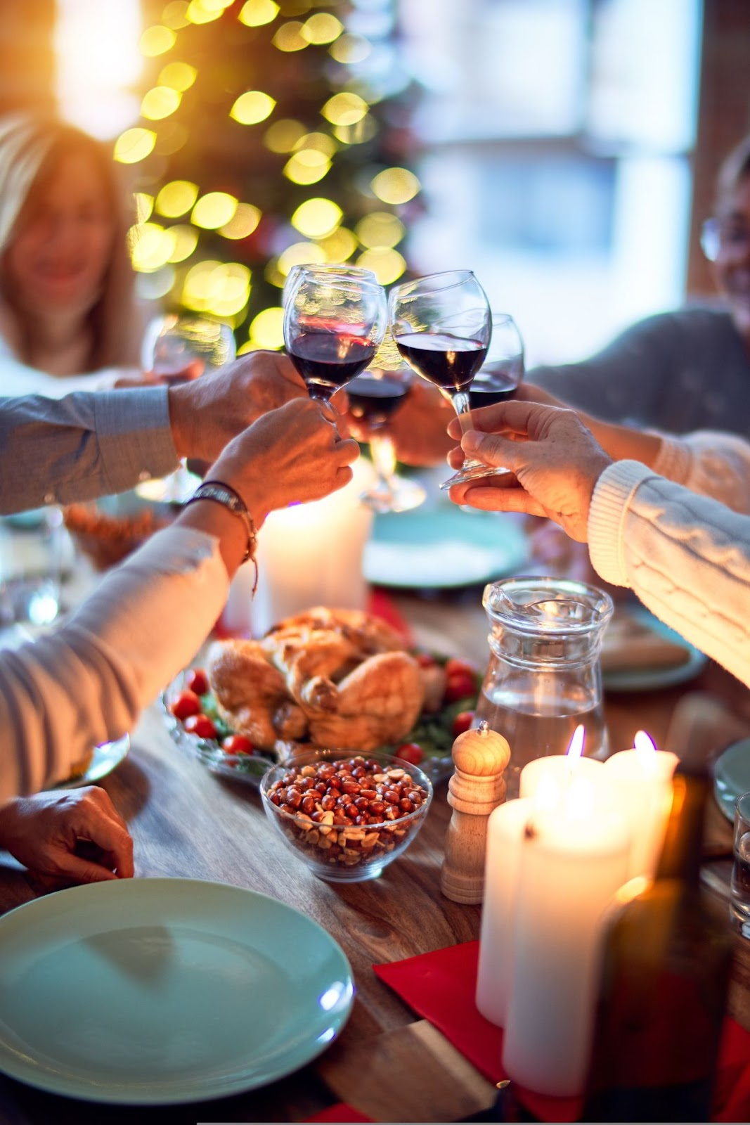 a group of people at a dinner table cheering their wine glasses together