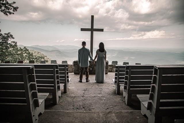 Couple standing in front of Cross overlooking landscape