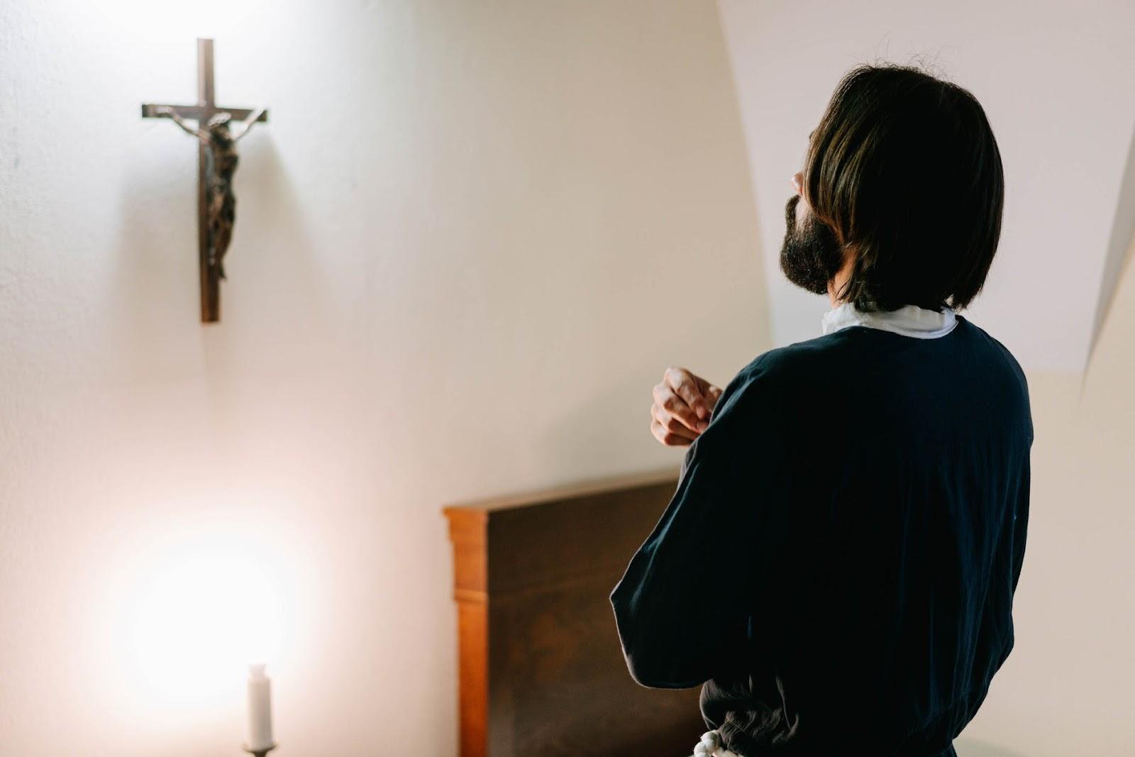 Man praying in front of crucifix