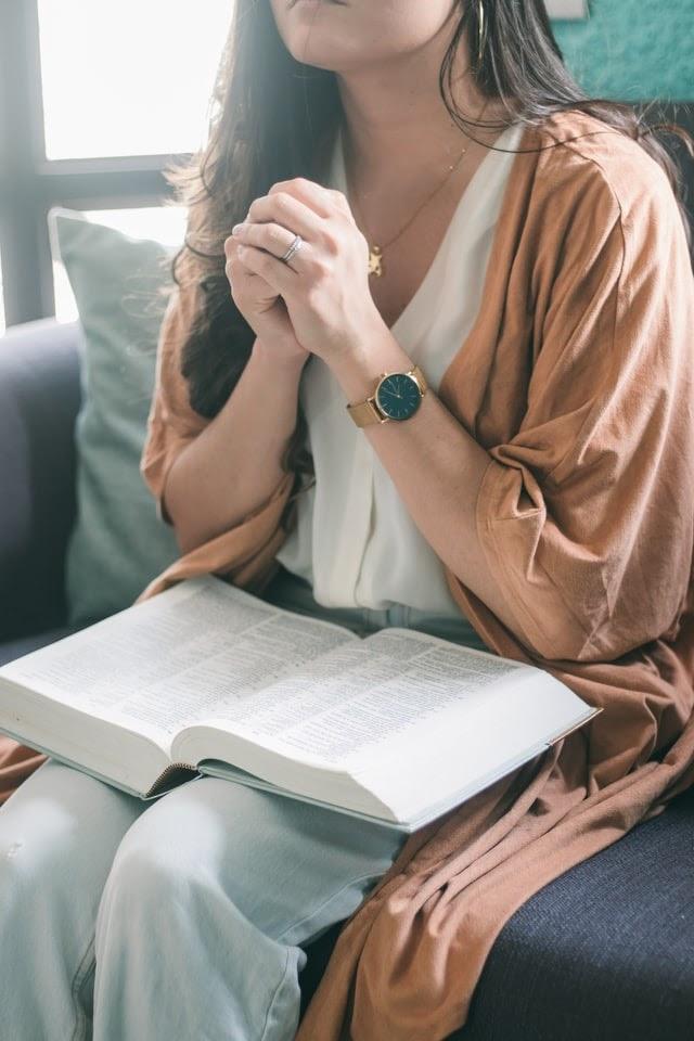 Woman praying with Bible on lap