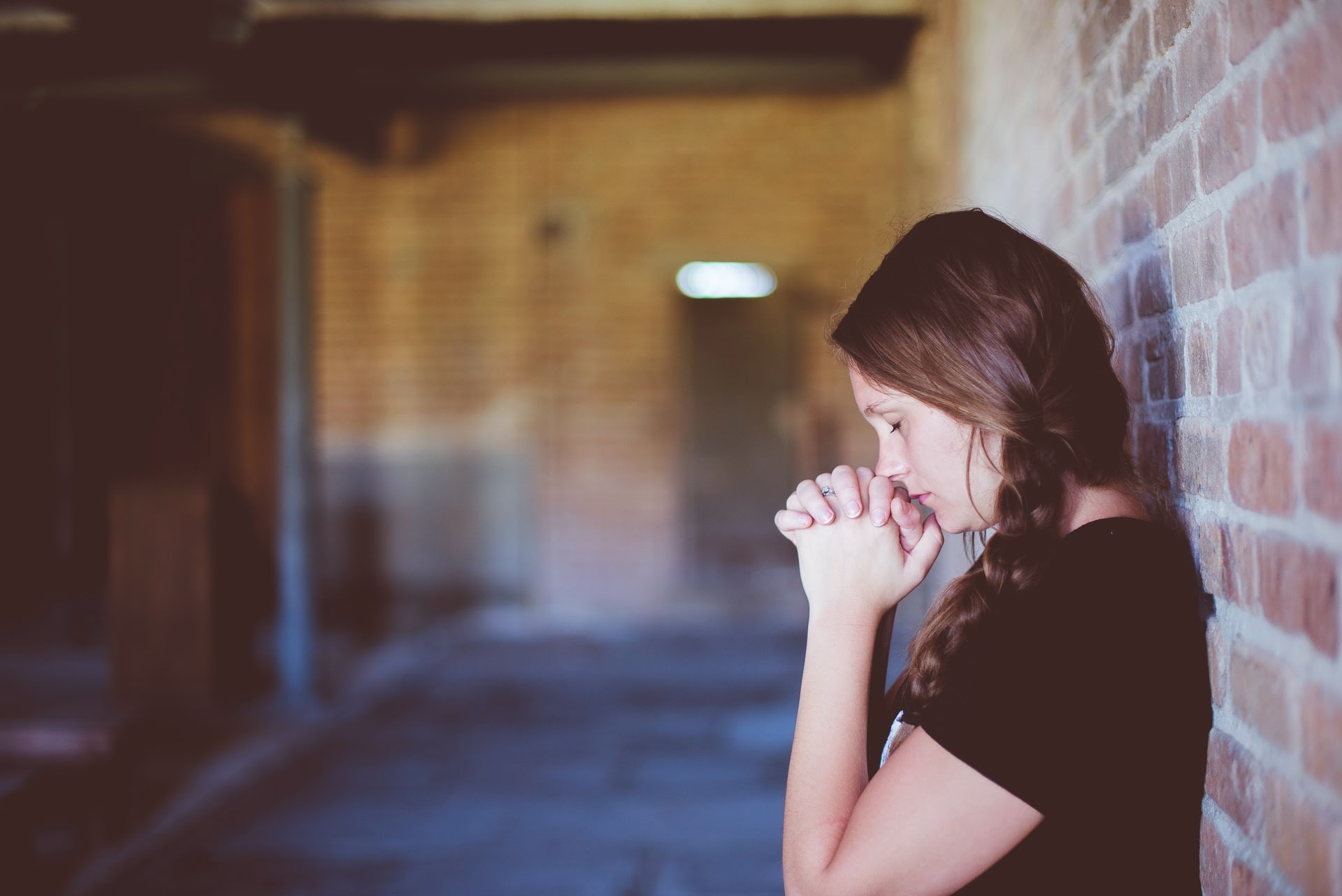 a woman leaning against a wall and praying