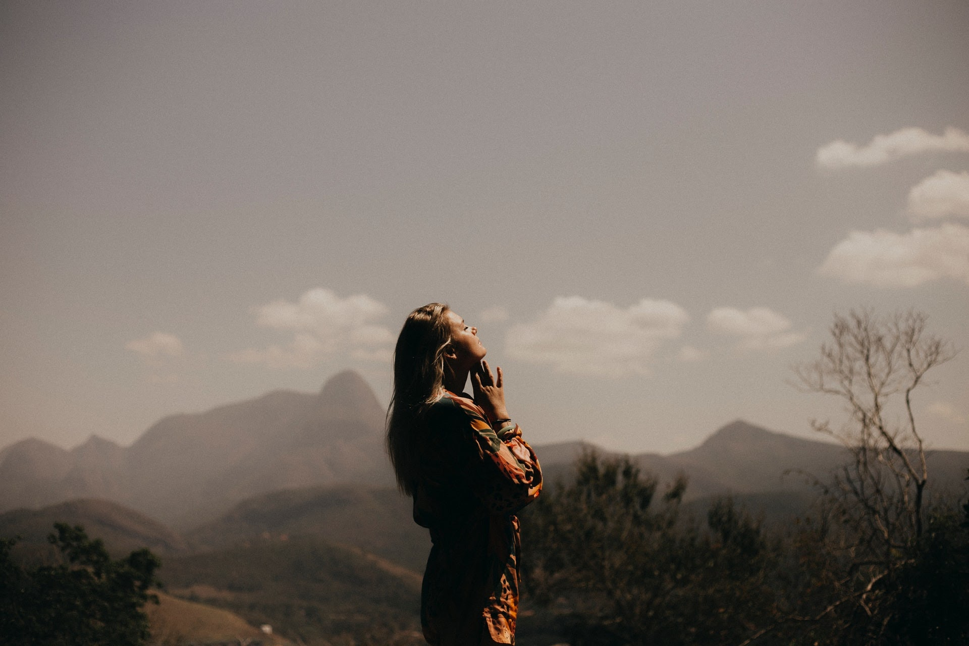 a woman standing in the mountains and praying