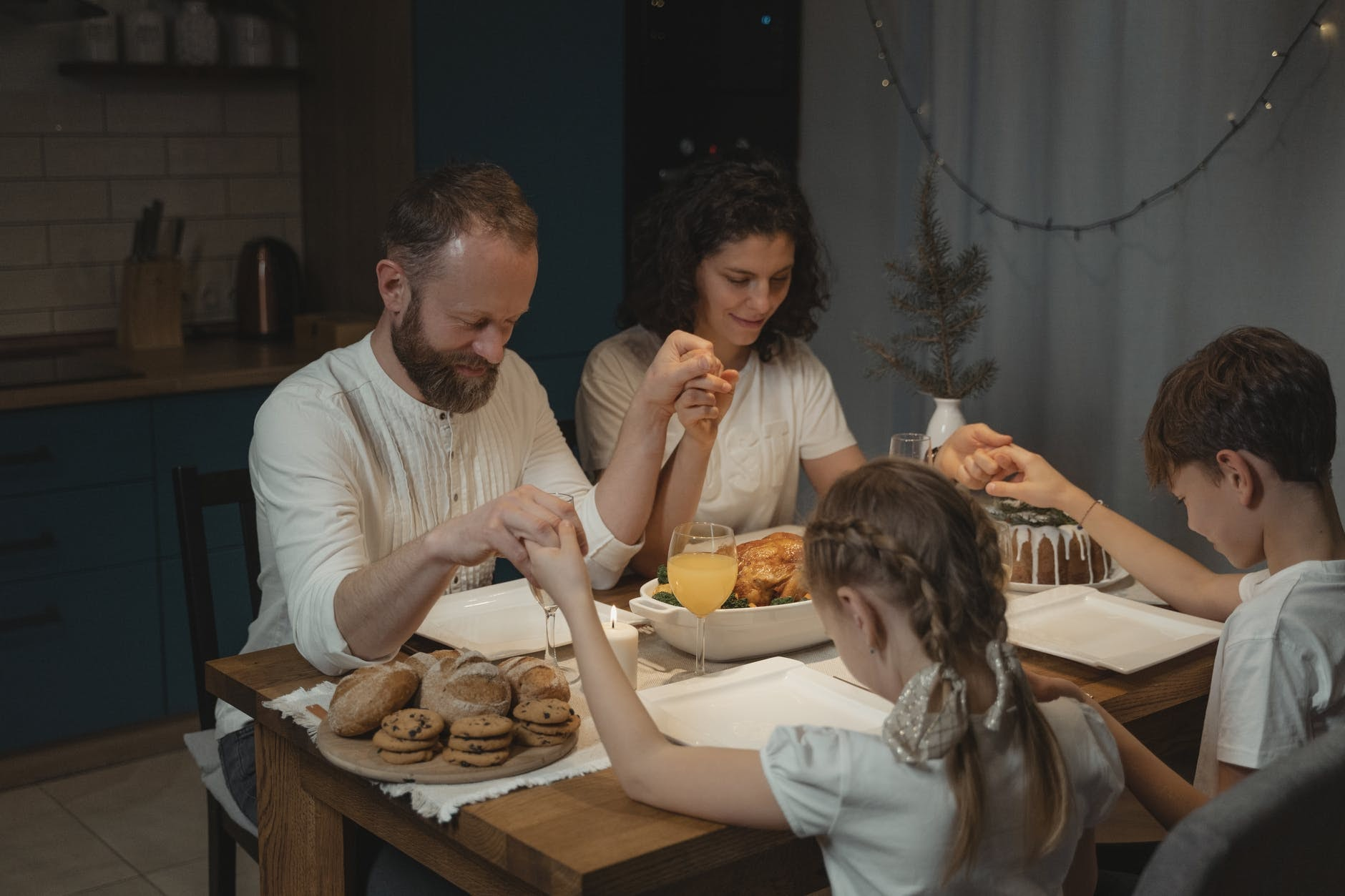 family holding hands in prayer around kitchen table
