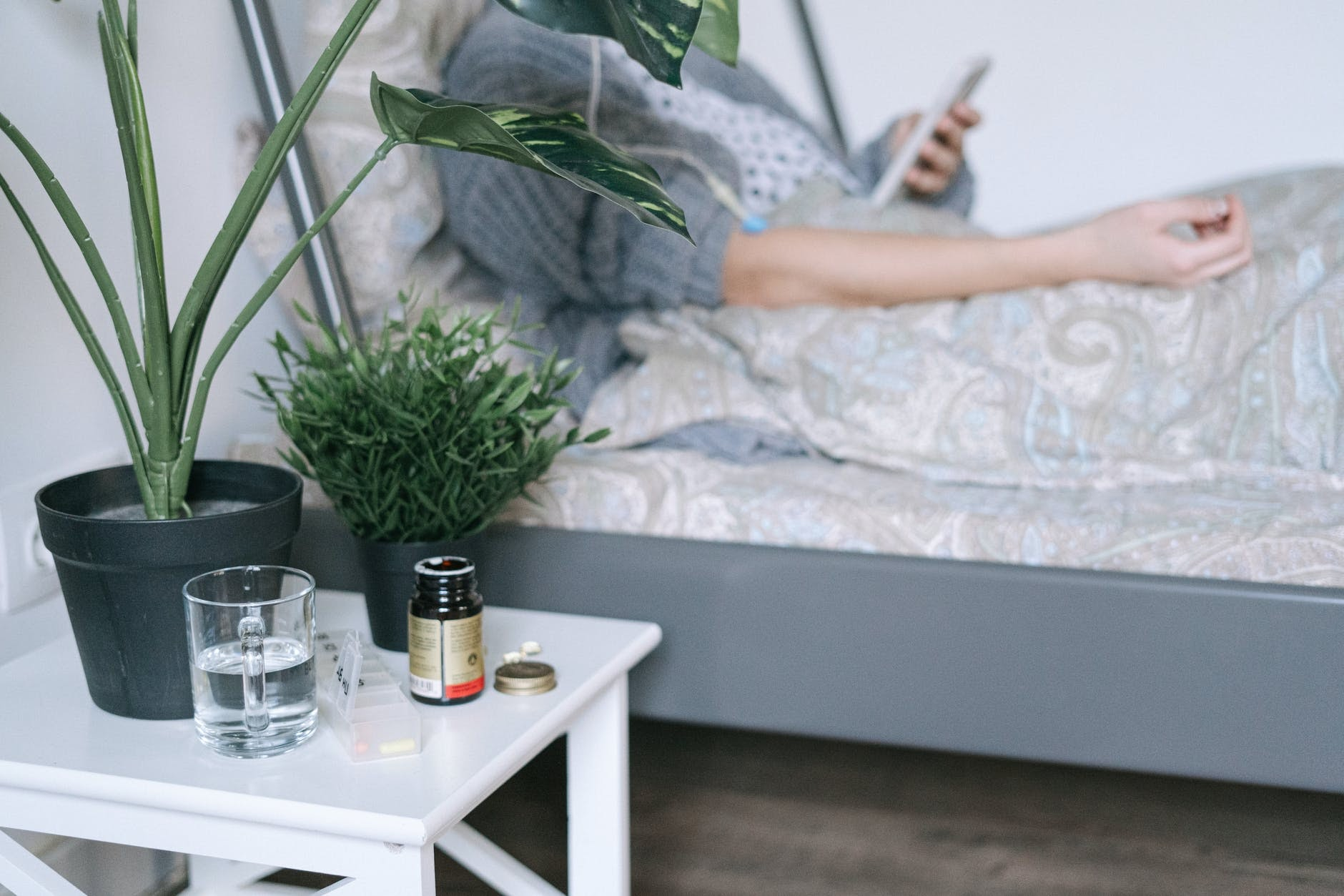 a person sitting in bed with medicine and a glass of water next to them