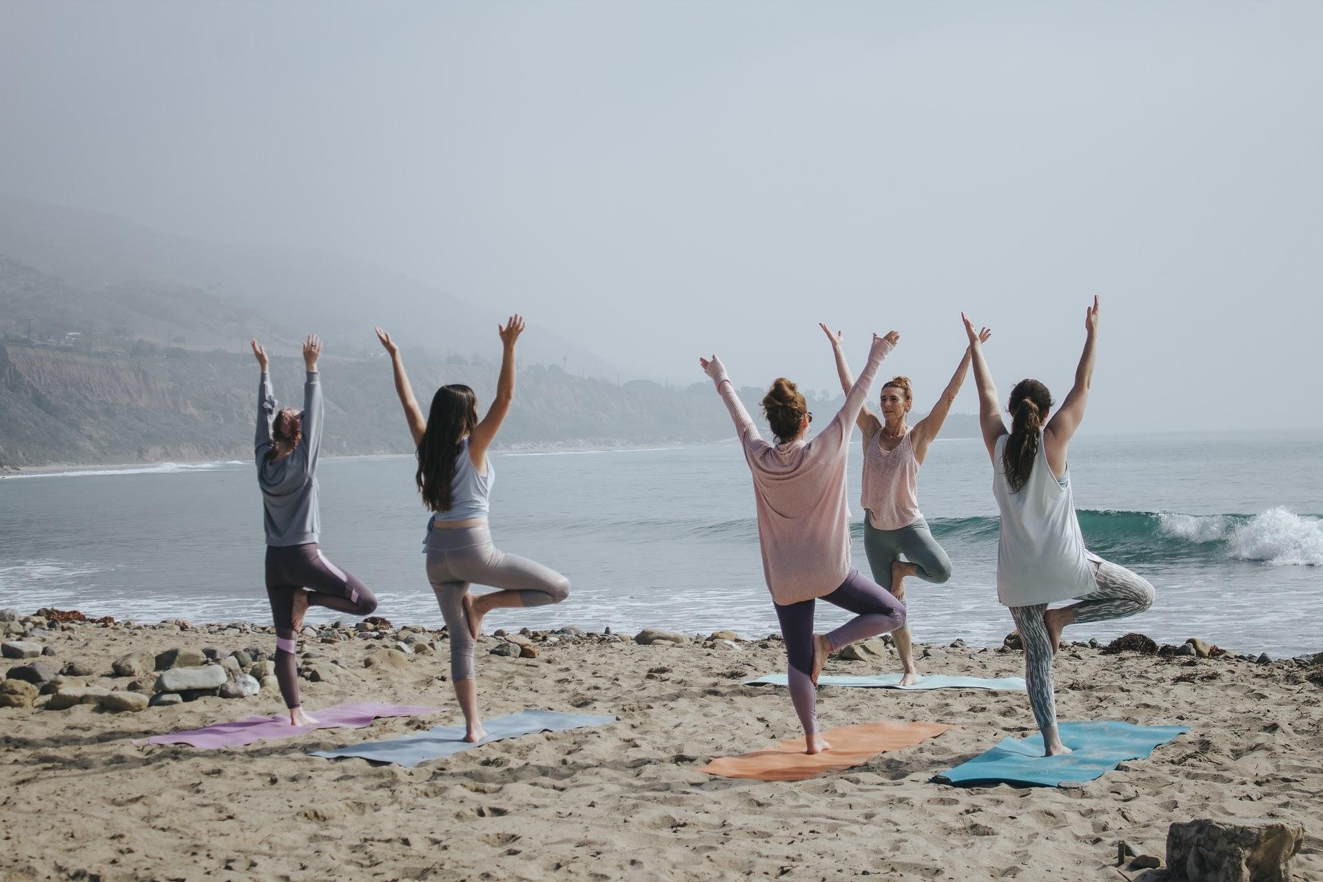 five women on a beach doing yoga