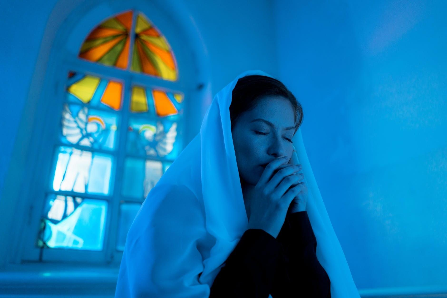 Woman in veil praying in dimly lit church.