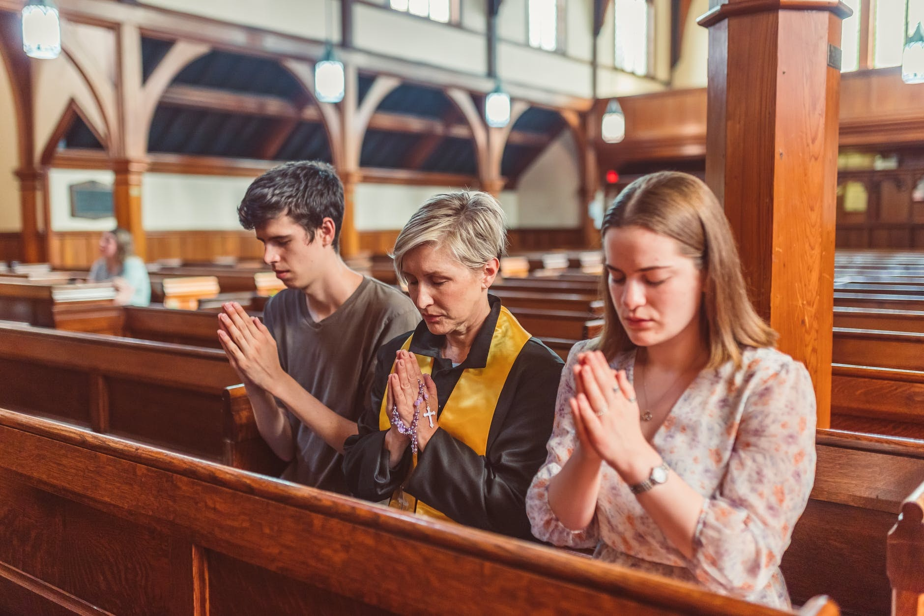 Three people praying together in church.
