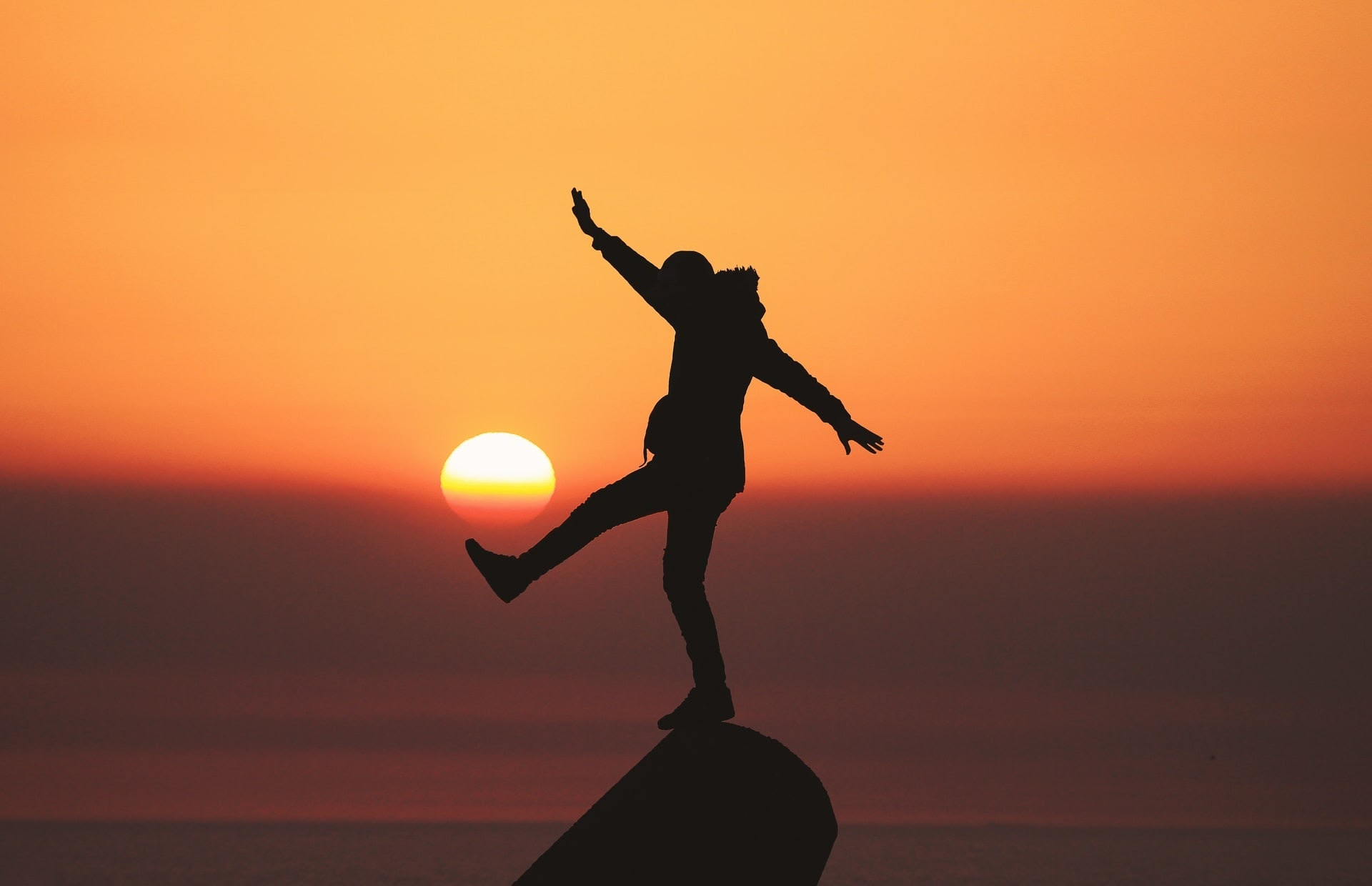 silhouette of a person balancing on something during a sunset