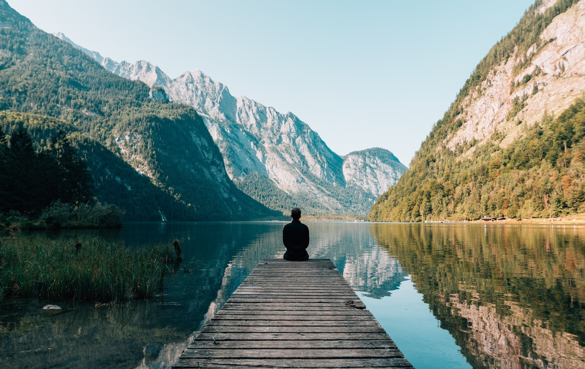 a person sitting on a pier on the water and looking out at the mountains