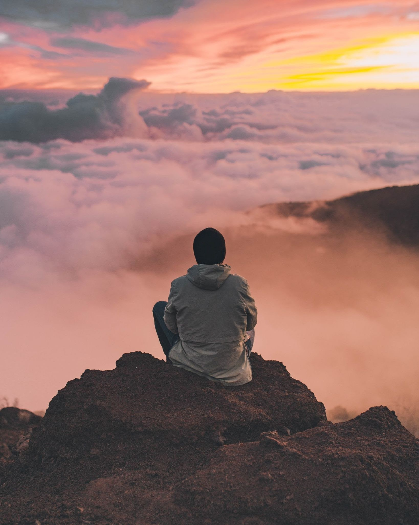 a person sitting on a rock and looking out at the clouds