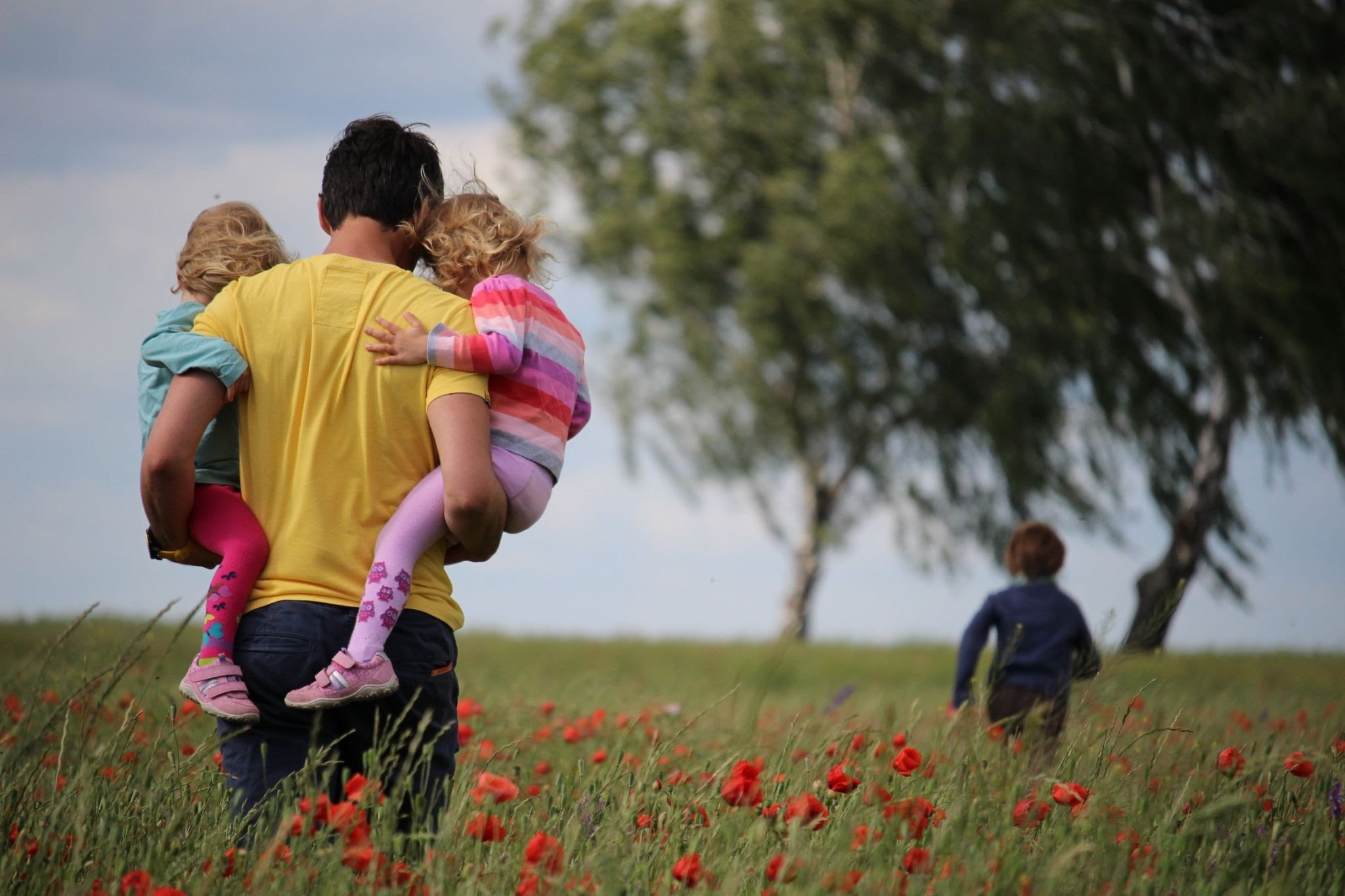 Man holding two children and walking in a field while another child runs ahead