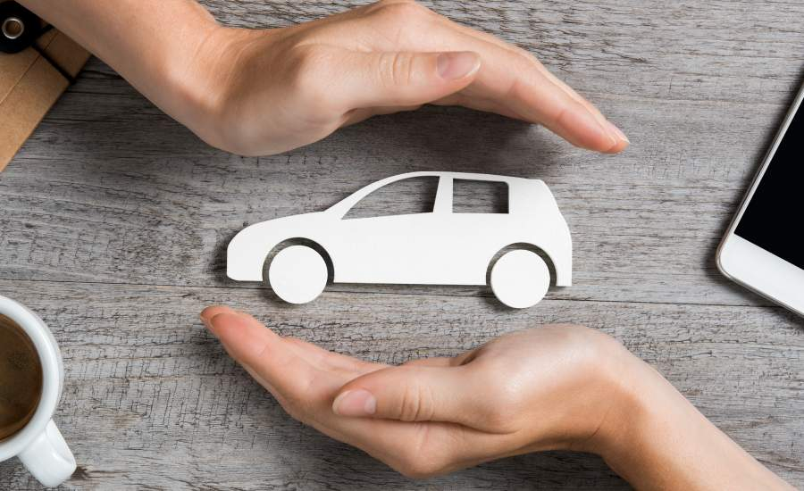 paper cut out of car framed by hands