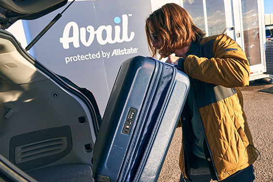 man putting suitcase in trunk at Avail lot
