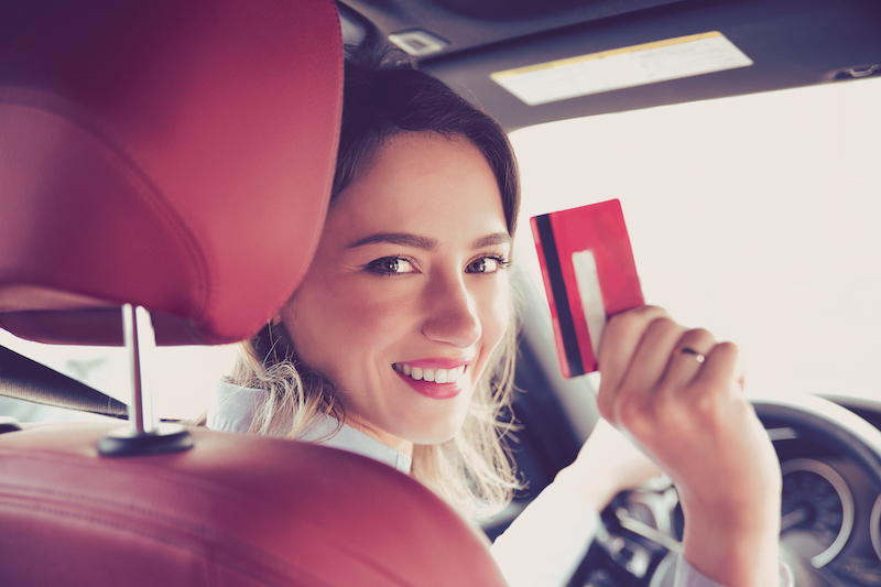 woman sitting in front seat of car with credit card