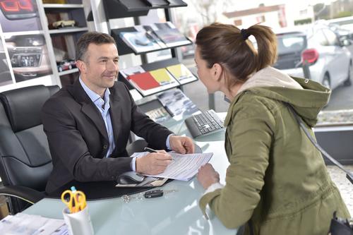 woman reviewing paperwork with car rental representative