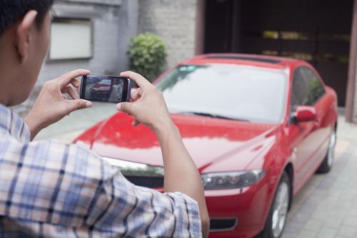 man reviewing rental car for damage