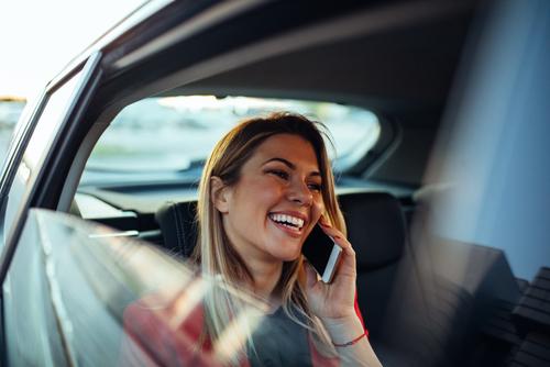 woman talking on phone in rental car