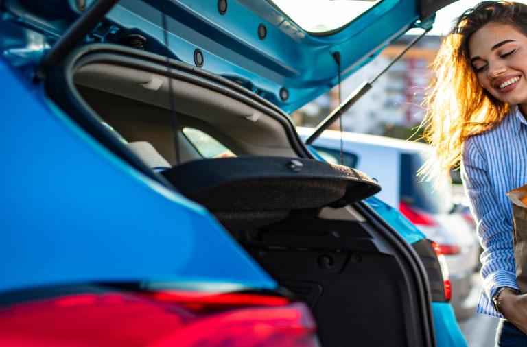 woman placing groceries in car