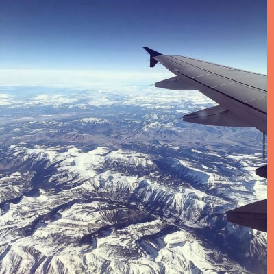 view from airplane window of snow capped mountains.