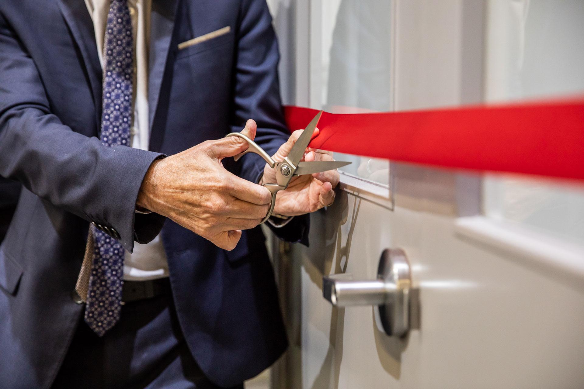 A hand cutting a ribbon