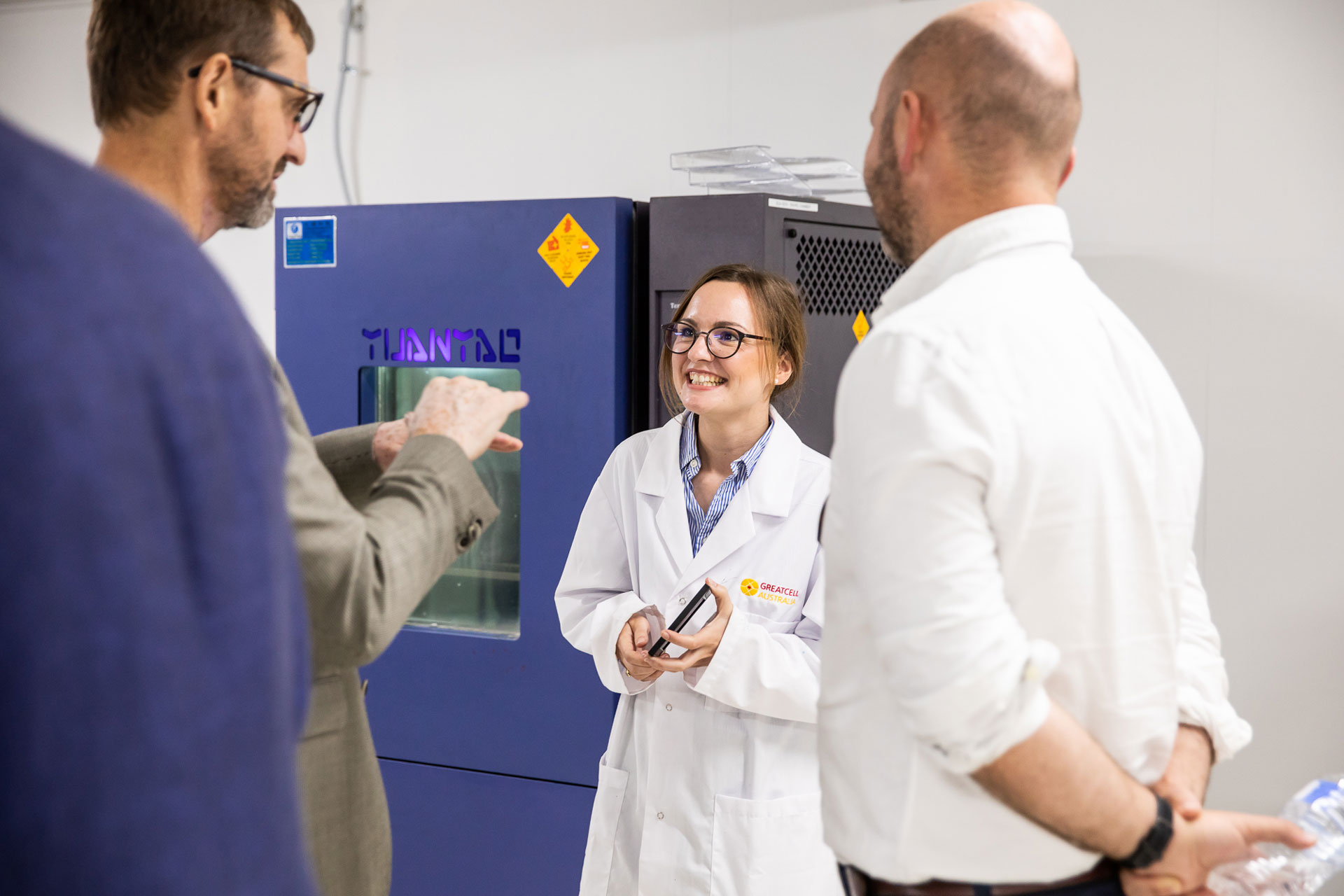 Group talking in front of laboratory equipment