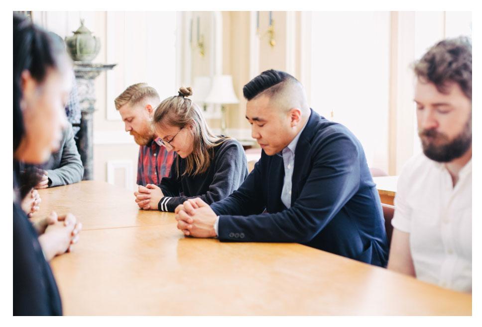 students praying at table