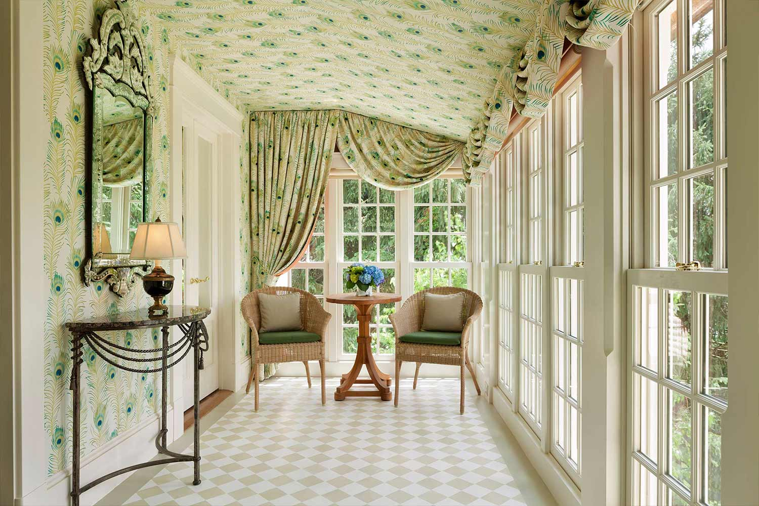 Room 14's private sunroom. Sunlight streams into the room with floor to ceiling windows and green wallpaper.