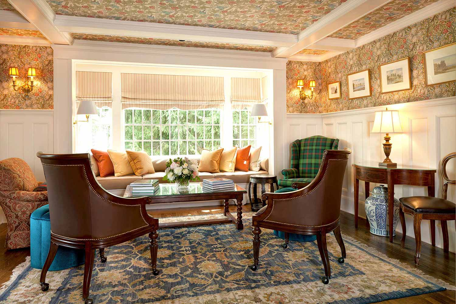 The common area living room in the Carter House with a bright bay window and antique furniture.