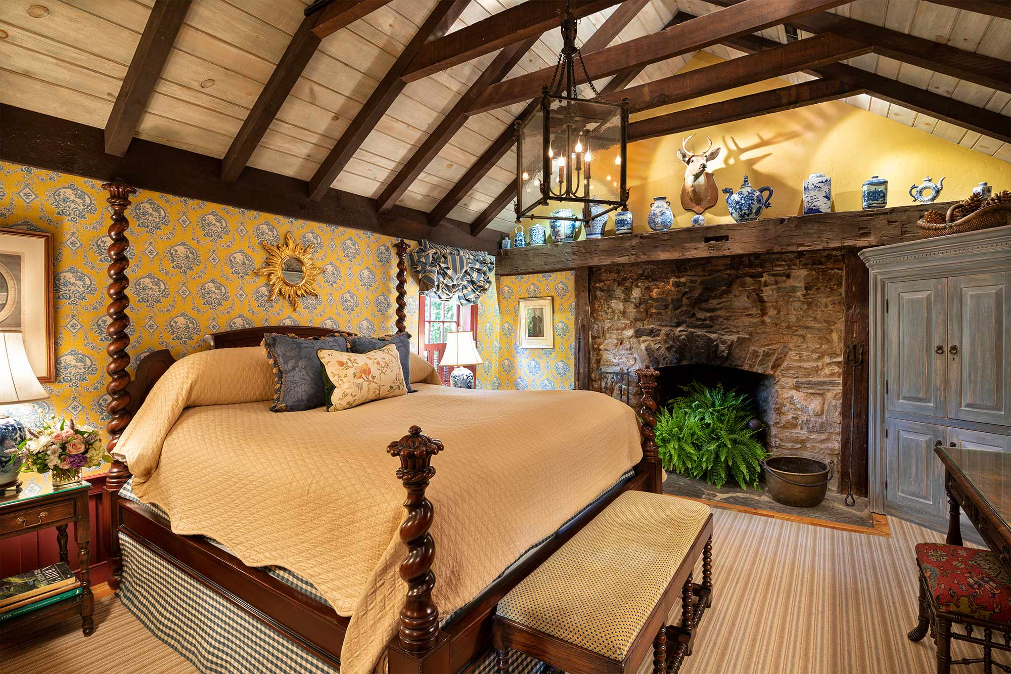 A large master bedroom with a king sized bed and large, stone fireplace.