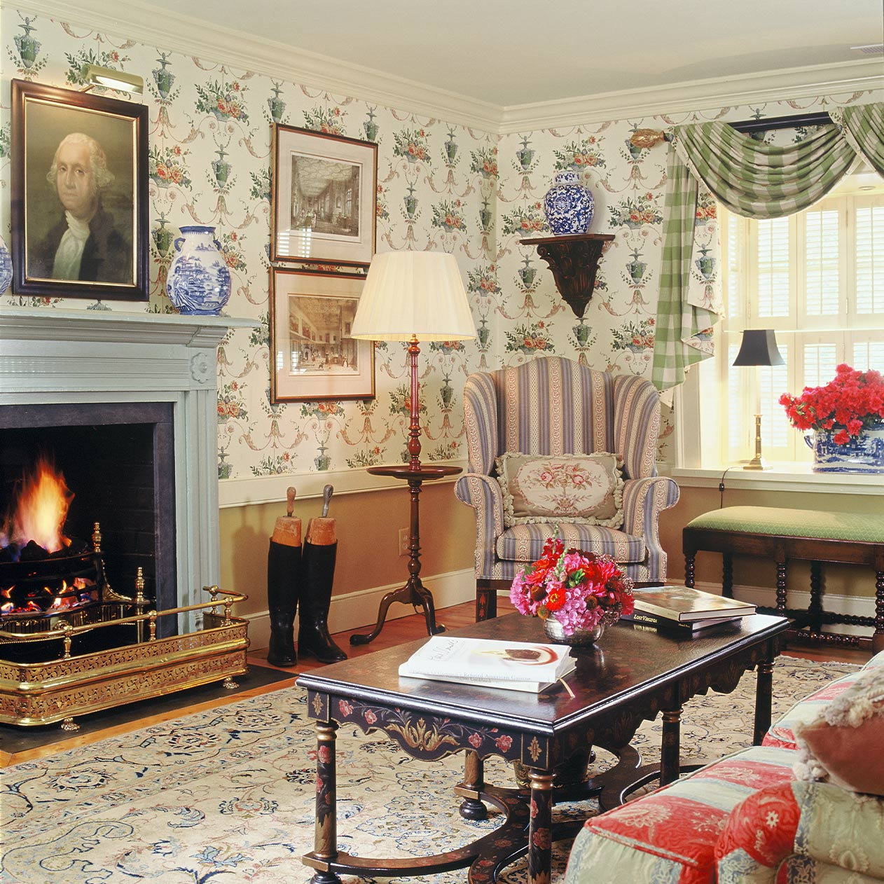A vintage living room featuring a fireplace, antique furniture and patterned wall paper.