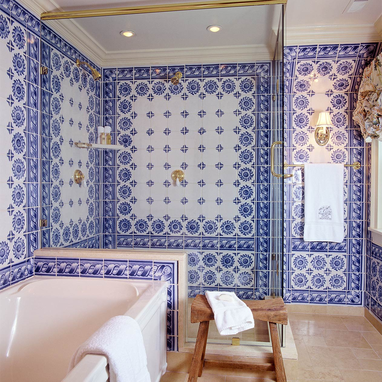 A large bathroom featuring a prominent soaking tub and separate walk in shower. The walls are made up of patterned, hand painted blue and white tiles.