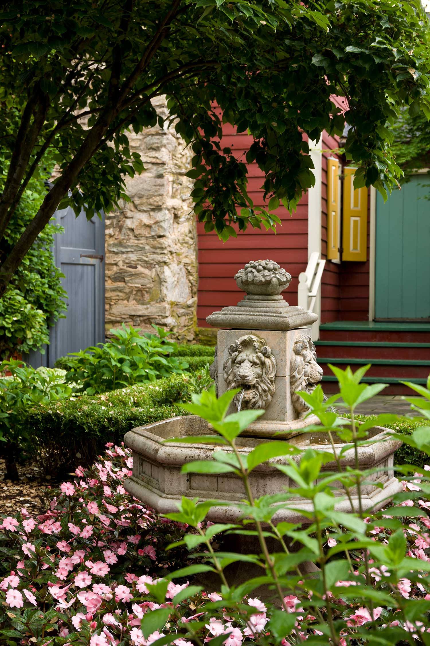 The Mayor's House garden with a stone fountain with a carved lion head on it. The fountain is surrounded by lush greenery and pink flowers.