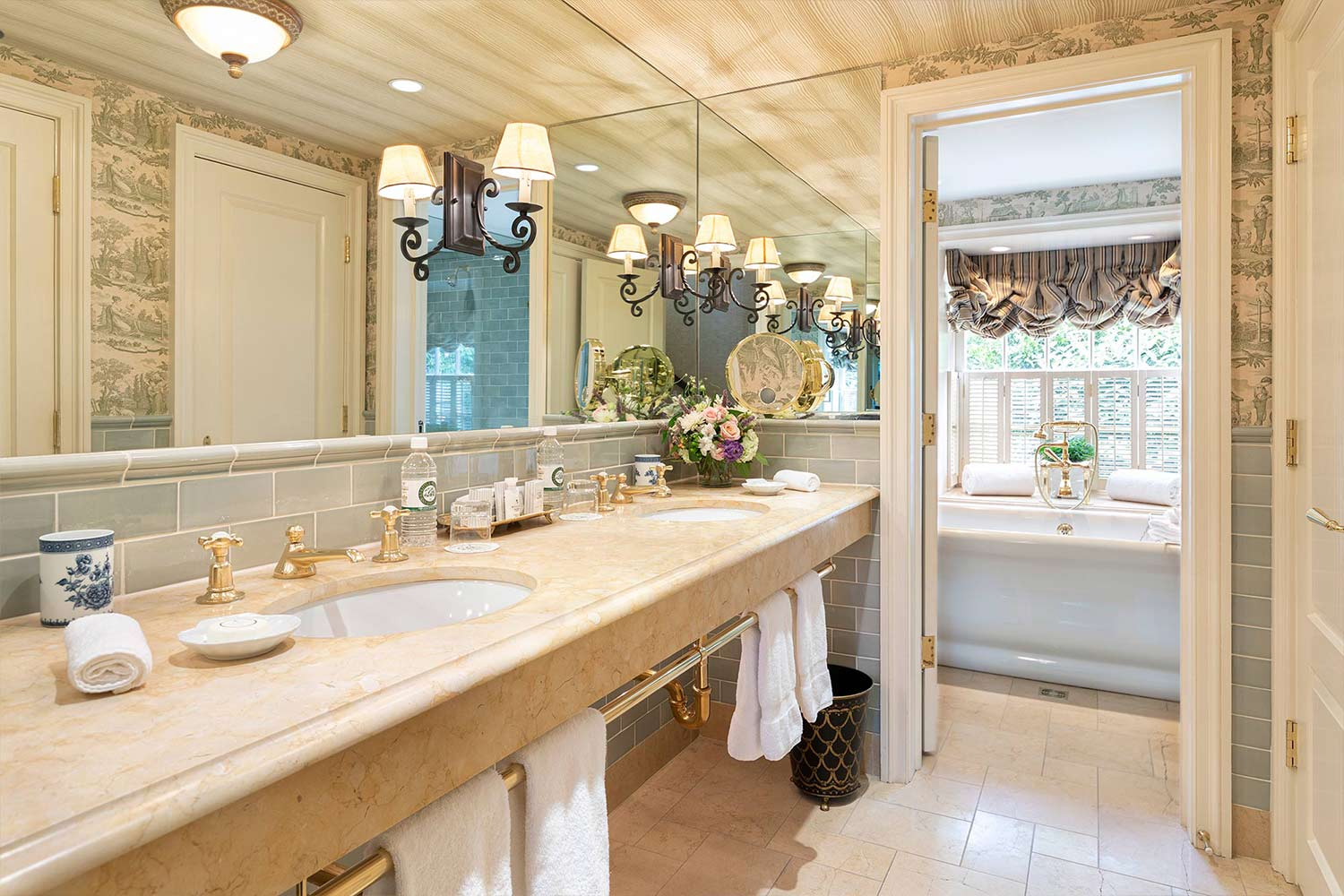 A bright bathroom with dual vanity sinks and a large soaking tub.
