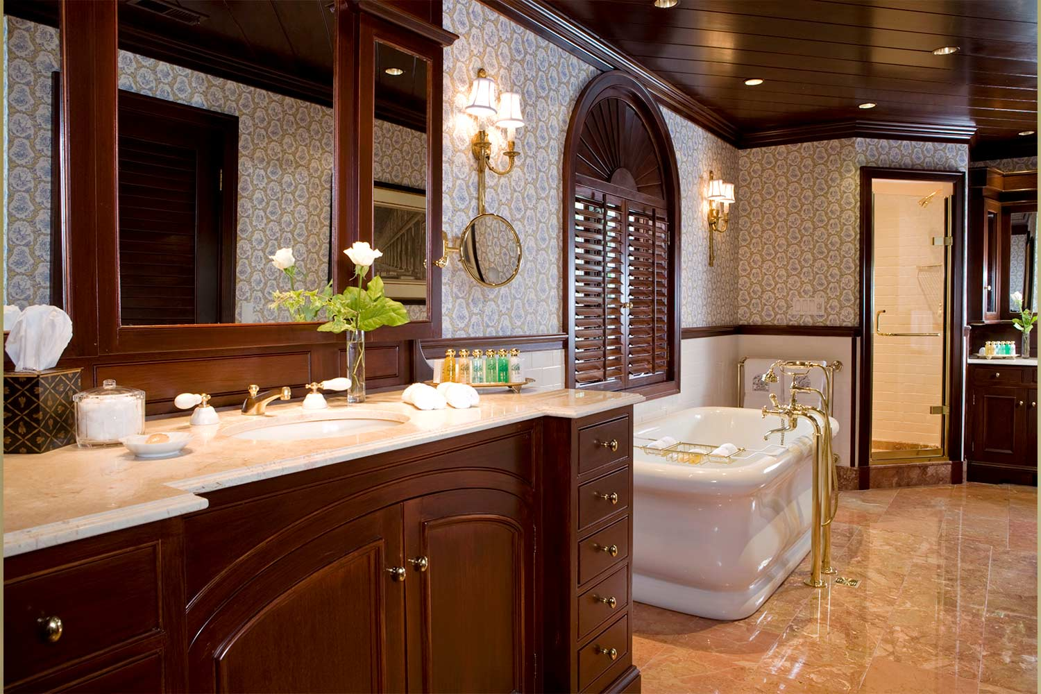 An oversized, luxurious bathroom with a large soaking tub, separate walk in shower and vanity with dark, rich woods and light countertops