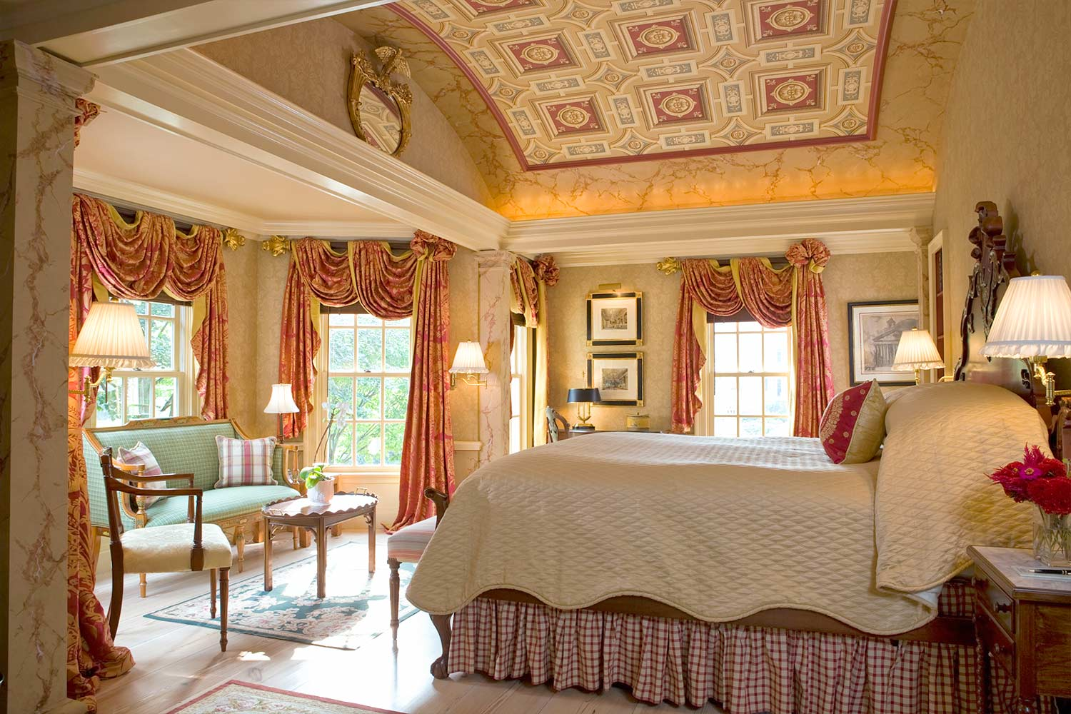 A very large master bedroom with a king sized bed, sitting area and ornate ceiling.