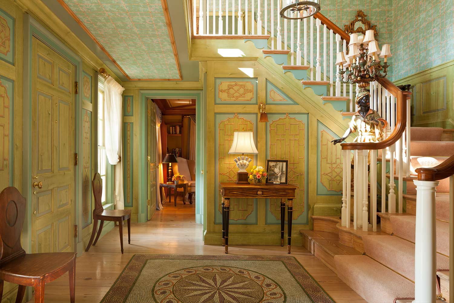 The foyer of the Claiborne House featuring a beautiful, wrap around staircase, hand painted green paneled walls and antique center rug.