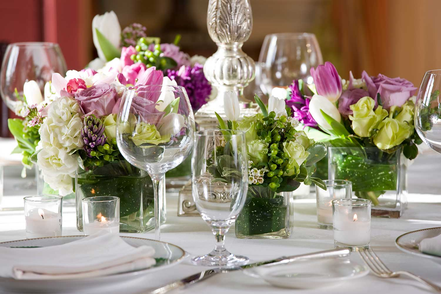An event table featuring pink flowers and empty wine glasses.