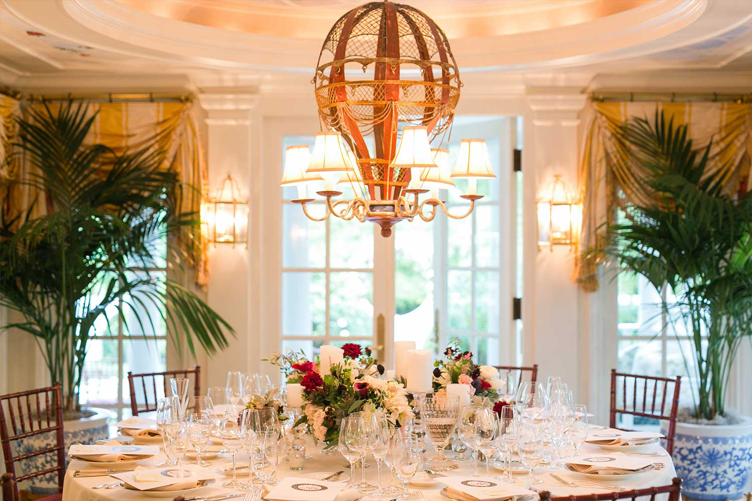 The dining room of the Claiborne House. A circular dining table surrounded by floor to ceiling windows overlooking a private garden. A chandelier in the shape of a hot air balloon is overhead.