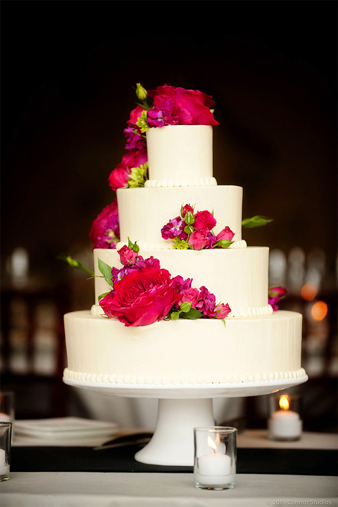 A three tier wedding cake with red flowers.