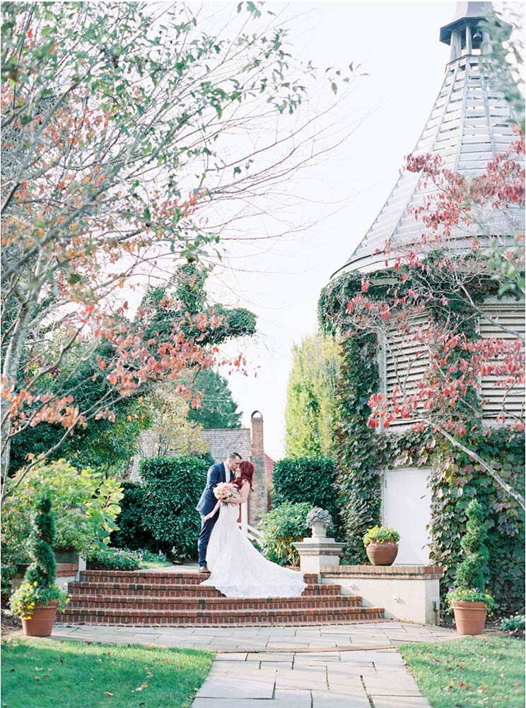 A groom dipping his bride and kissing surrounded by the lush grounds at The Inn.