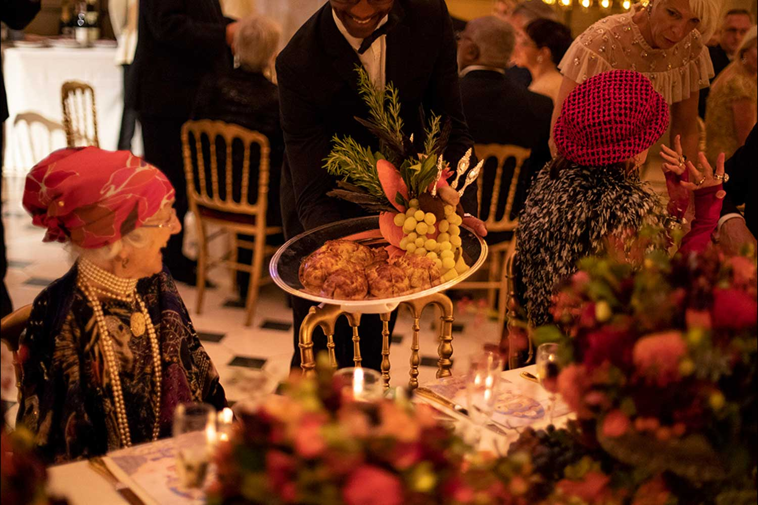 Designer Joyce Conwy Evans smiling at the presentation of food at an event. The table is set with autumnal flowers and food.