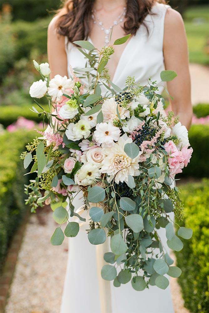 A closeup of a bride holding a stunning floral arrangement.