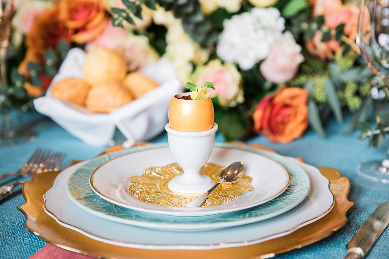 A table set for a wedding featuring a golden egg, colorful floral arrangement and blue table cloth.