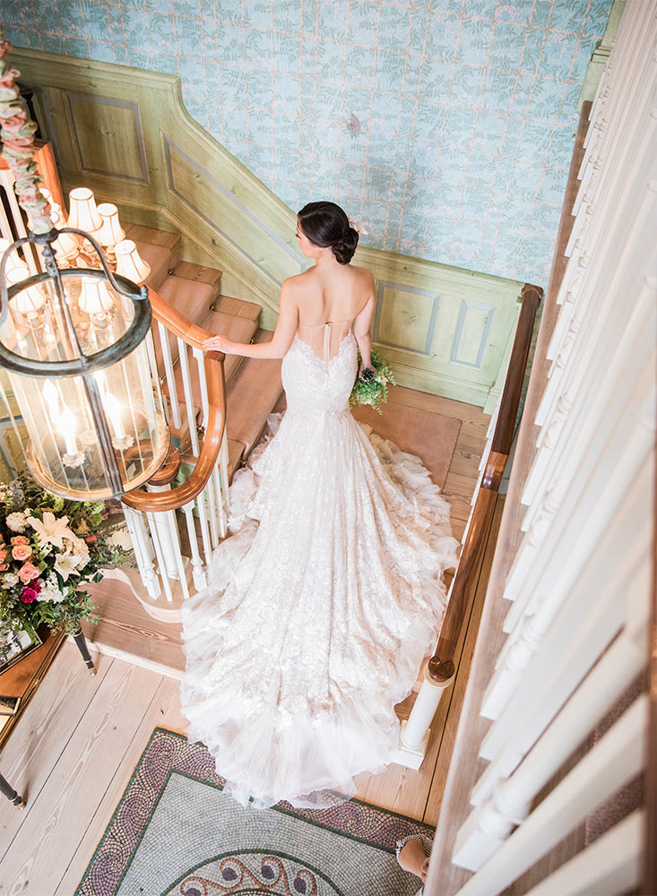 A bride with a flowing white gown walking down the stairs in the Claiborne House.