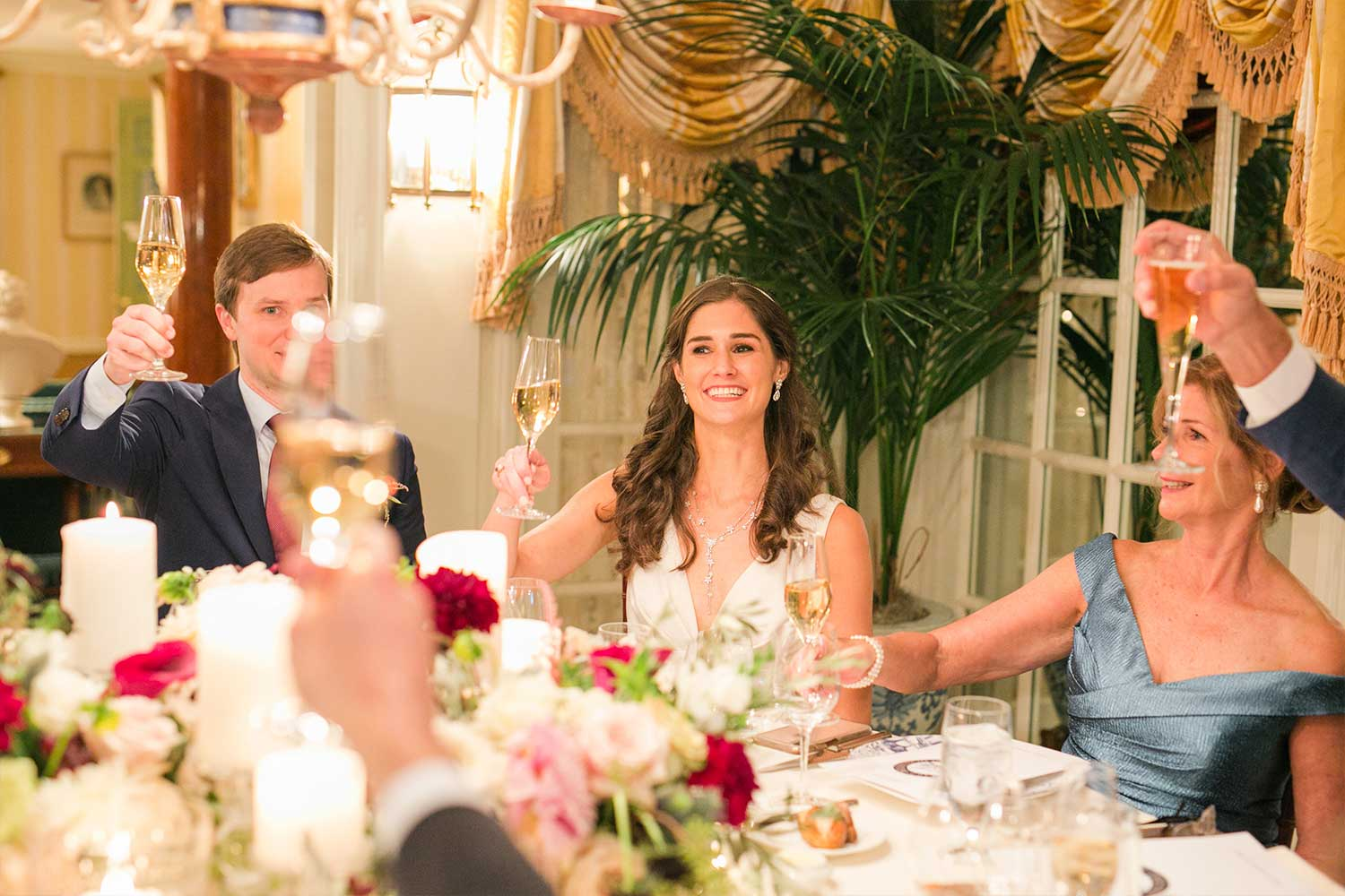 A family smiling and laughing at a wedding reception in the dining room of the Claiborne House.