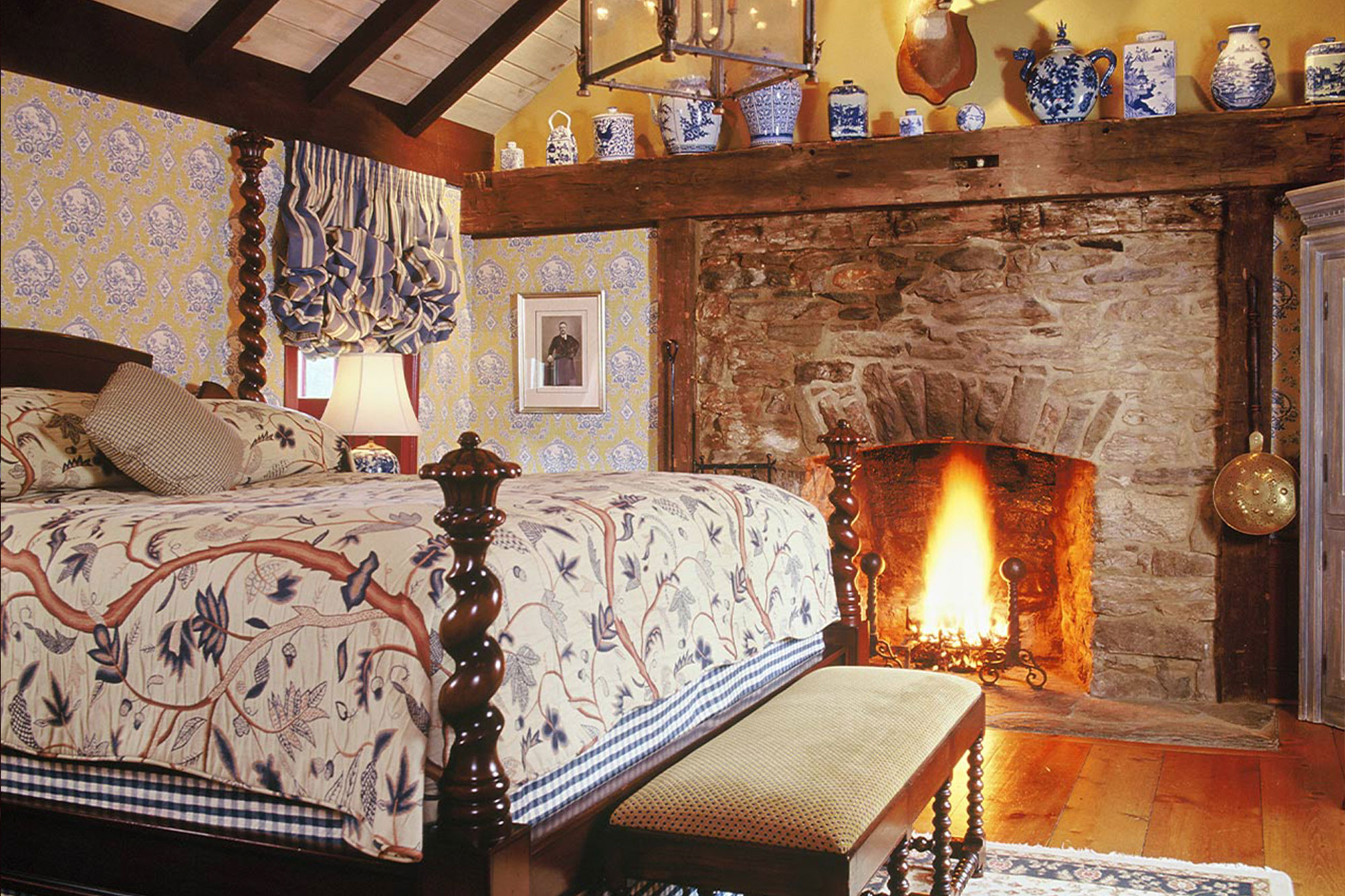 A large master bedroom featuring hardwood floors, a king sized bed and large stone fireplace with a blazing fire inside.